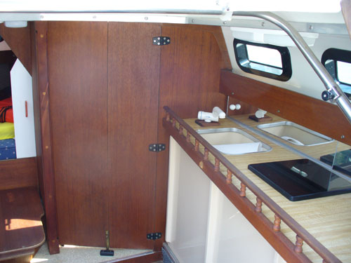 1998 Rhodes 22, starboard side of cabin has the enclosed head and countertop with sink and stove