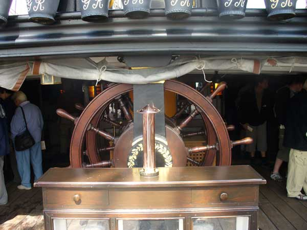 The wheel, with the captains's cabins behind it.  Turning the wheel moved the tiller from side to side and turned the rudder using ropes.